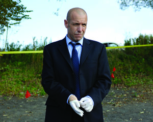Detective Mike Sweeney (Hugh Dillon) at the lakeshore murder site.