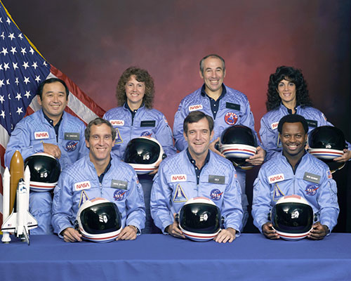 Space Shuttle Challenger STS-51L crew members: in the back row from left to right: Mission Specialist, Ellison S. Onizuka, Teacher in Space Participant Sharon Christa McAuliffe, Payload Specialist, Greg Jarvis and Mission Specialist, Judy Resnik. In the front row from left to right: Pilot Mike Smith, Commander, Dick Scobee and Mission Specialist, Ron McNair.